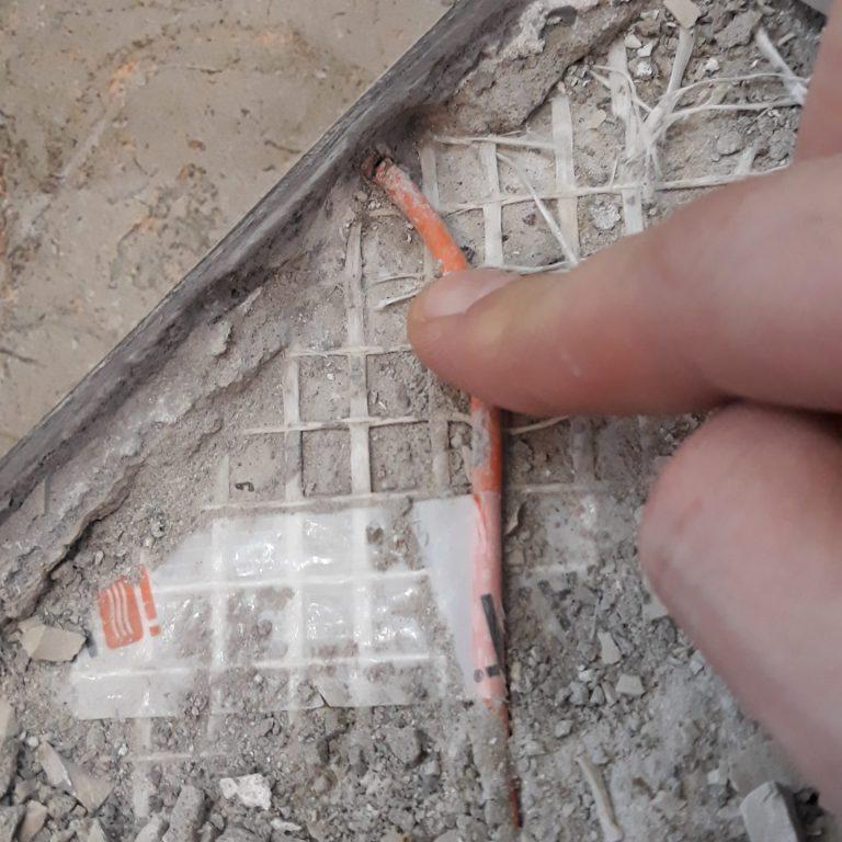 Греющий кабель порезан ножом по шву плитки